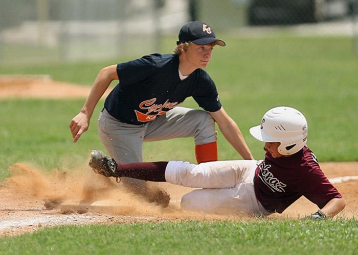 Young baseball player sliding into a base