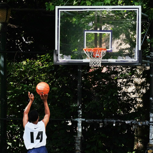 Person playing basketball in a park